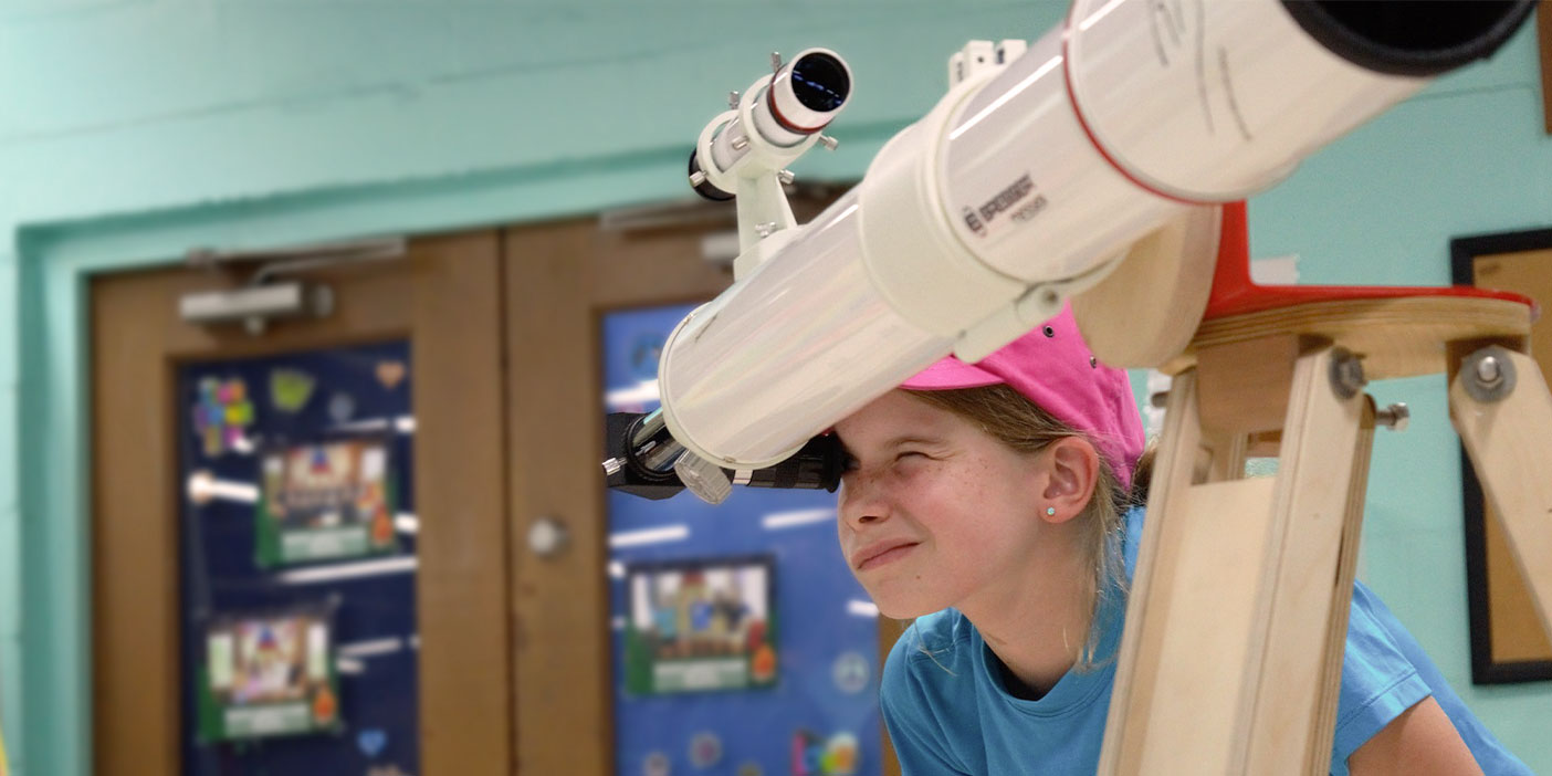 A young kid wearing a pink baseball cap is bending down to have a look through a big telescope.