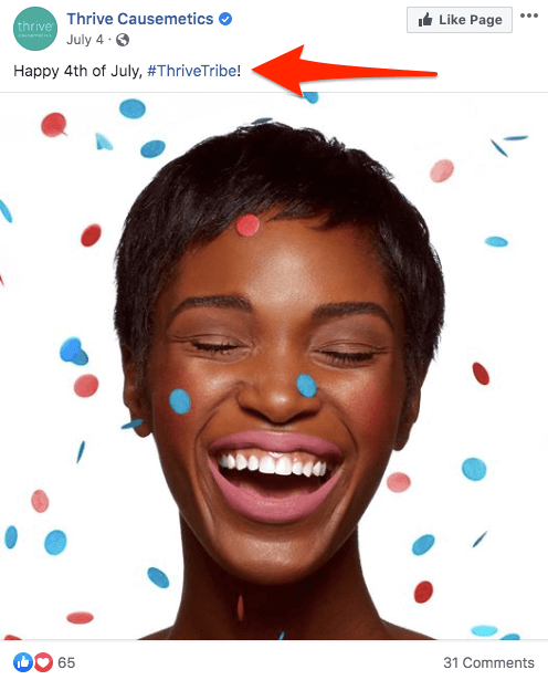 "A Facebook post by Thrive Causemetics: ""Happy 4th of July, #ThriveTribe!""  The image is a headshot of a person with short dark hair, laughing with closed eyes. Confetti is photoshopped in over the face and white background."