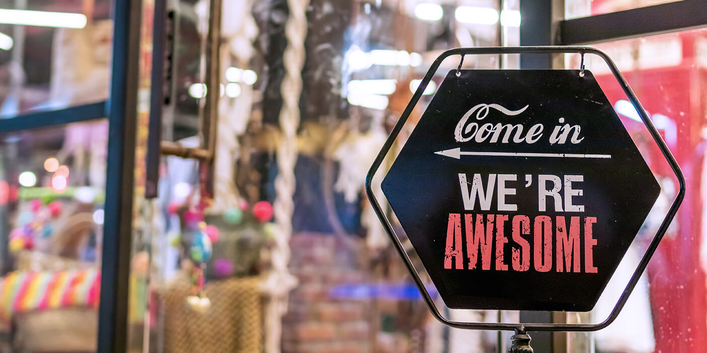 "Sign in front of a shop that says ""Come in. We're awesome"", with an arrow pointing towards the shop entrance."