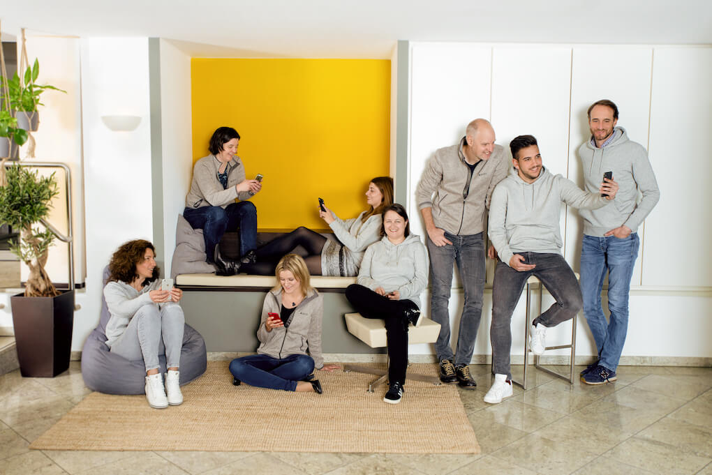 A group of eight people milling around in and in front of a sitting nook. They're all wearing grey hoodies or zip up jumpers and holding smartphones.