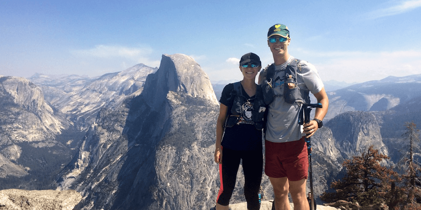 Two people in hiking gear and reflective sunglasses are happily smiling from ear to ear as they?re posing for a photo at the top of a summit with an impressive mountain range behind them.
