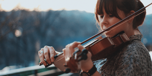 Close-up of a person playing the violin on a balcony. The trees in the background are blurred.