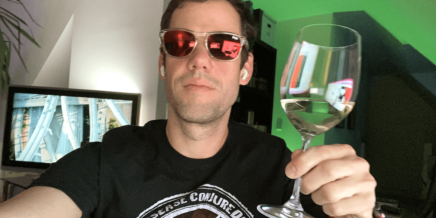 Walls.io CEO Michael taking a selfie at his desk while wearing sunglasses and holding up a glass of wine.