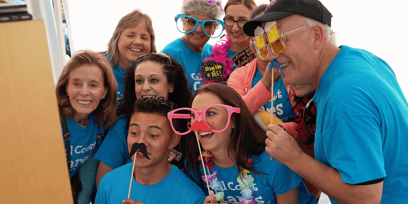 A group of people in bright blue t-shirts are posing in front of a photo booth with funny props like huge glasses and moustaches on a stick.
