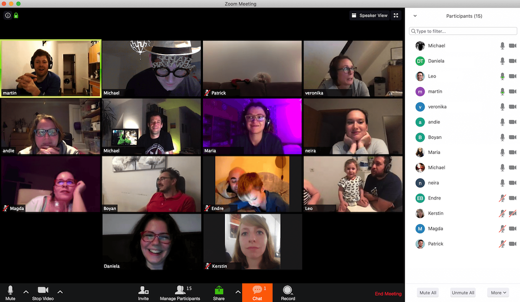 Screenshot of a Zoom.us call with 14 participants. We see people's smiling faces. Some of them have dressed up a bit with funny glasses or tiaras, some are holding a glass of wine.