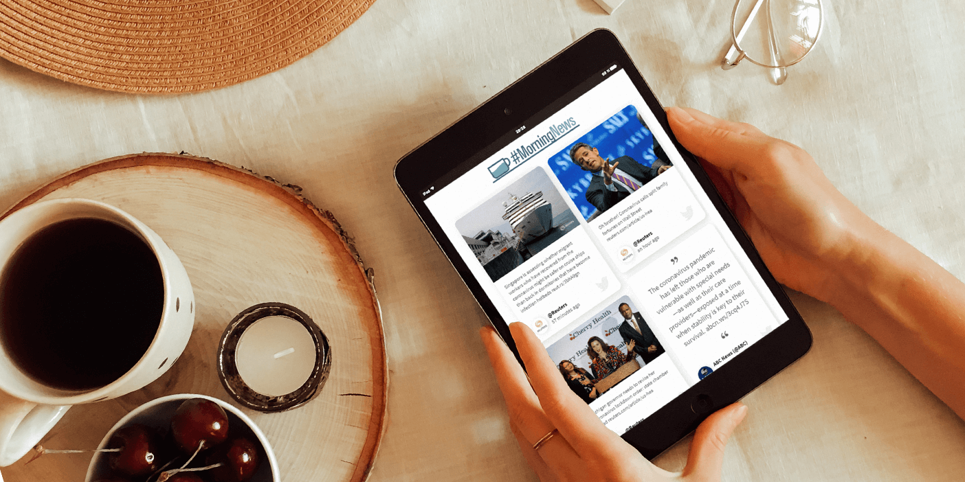 Two hands resting on a tablecloth, holding a tablet which displays a social wall news feed under the title ?#MorningNews. Next to the hands on the left side, we see a small round wooden serving tray holding a cup of coffee, a bowl of cherries and an unlit tea light.