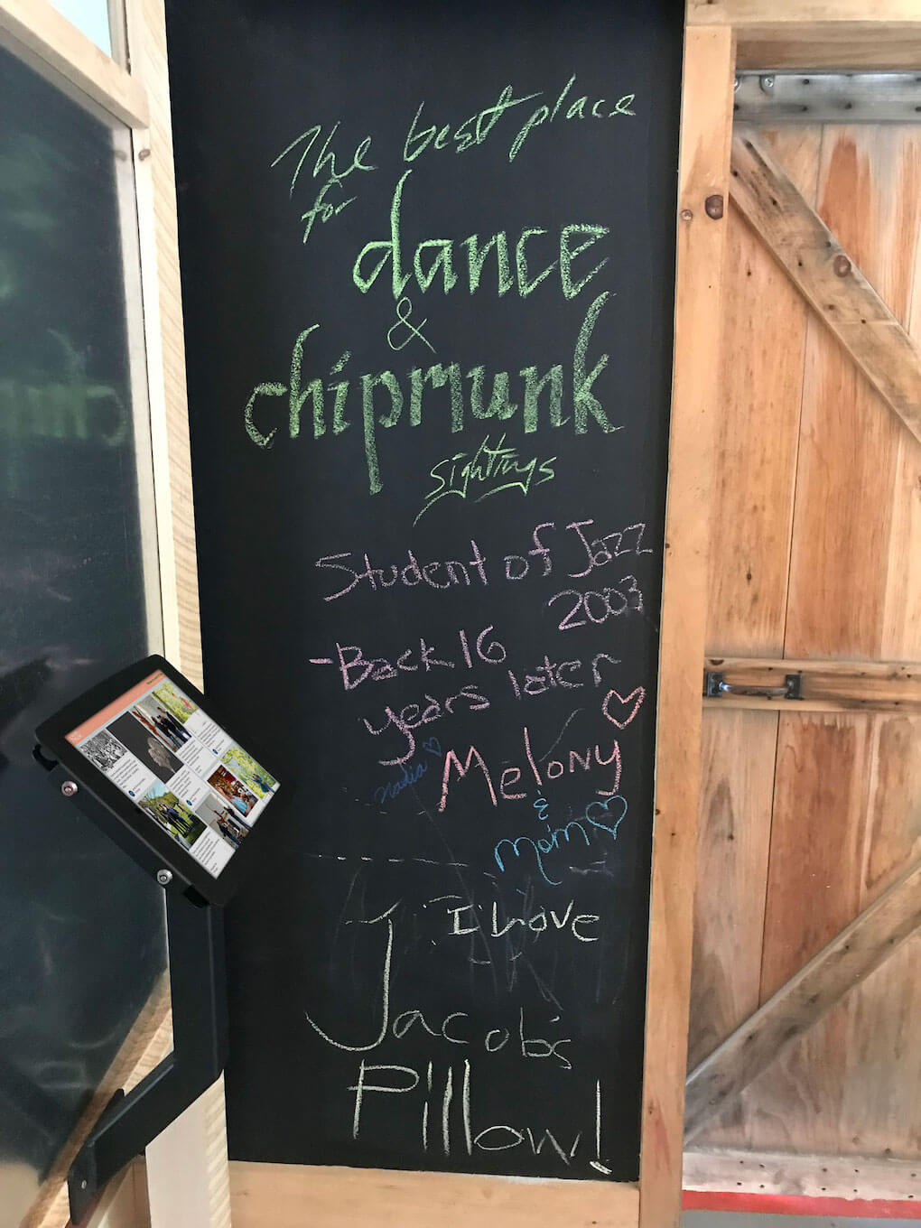 An iPad showing the Jacob's Pillow social media wall is mounted in front of a blackboard with scribbled messages at the Jacob's Pillow Welcome Center.
