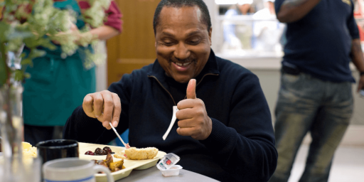 Person is sitting at a table and eating from a beige tray, holding plastic cutlery in their right hand. While looking at their food tray, they have a big smile on their face and are giving the camera a thumbs up with the left hand.