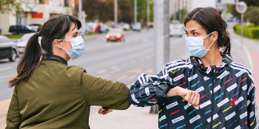 Two people wearing face masks and greeting each other by tapping their elbows together.