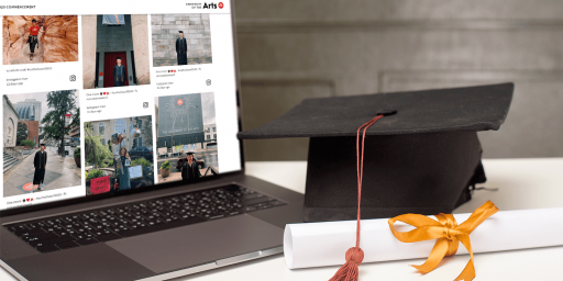 An open laptop showing a social media wall. Next to the laptop, a mortarboard graduation cap is placed next to a rolled up piece of paper with a yellow bow around it.