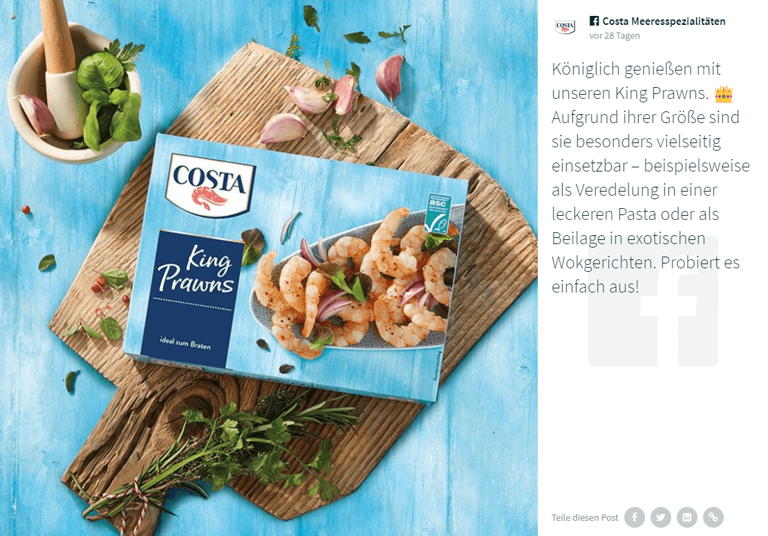 "A Facebook post by COSTA Meeresspezialitäten showing a box of COSTA's King Prawns product, placed on a wooden board on the same light blue wooden background as the post screenshot above. There's a small mortar and pestle with some herbs in it next to the board. Everything is decorated with green herbs strewn about.  The caption is in German and reads: ""Königlich genießen mit unseren King Prawns. 👑 Aufgrund ihrer Größe sind sie besonders vielseitig einsetzbar – beispielsweise als Veredelung in einer leckeren Pasta oder als Beilage in exotischen Wokgerichten. Probiert es einfach aus!"""