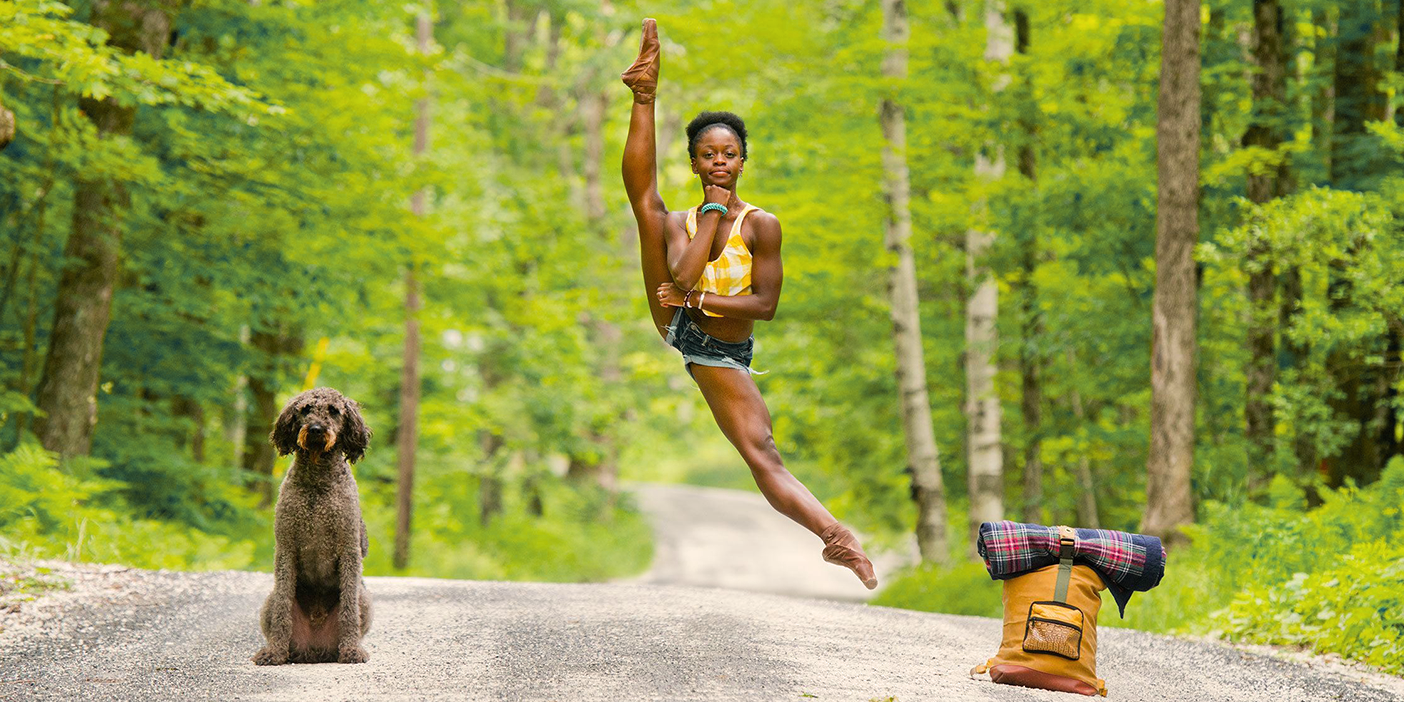 In the middle of a quiet country road surrounded by lush greenery on both sides of the street, a dancer jumps high in the air. Their legs are fully extended, one up next to their head, the other one stretched downward. The dancer is cheekily resting their chin on a hand. To one side of the person, a poodle sits on the road looking straight at the camera. On the other side of them, there's a yellow backpack with a blanket strapped to its top.