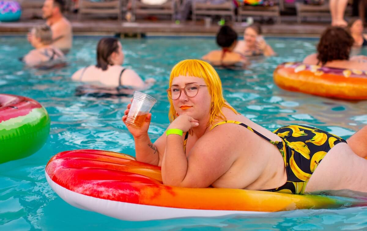 A plus-size person is lying on a colourful inflatable in a pool. She's confidently looking at the camera. Her chin is resting on one of her hands, in her other hand she's holding a drink in a plastic cup. In the background, other plus-size people are having fun in the water. Walls.io free stock photo sites collection.