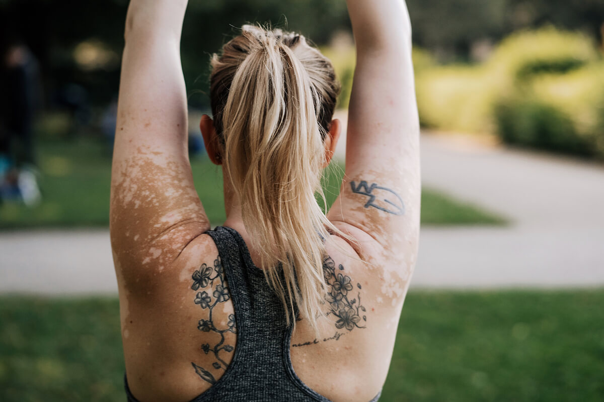 A white person shown from the back as she's stretching her arms up in the air. She's wearing a racerback top that shows a tattoo on her back and arm as well as her skin's hyperpigmentation. Walls.io free stock photo sites collection.