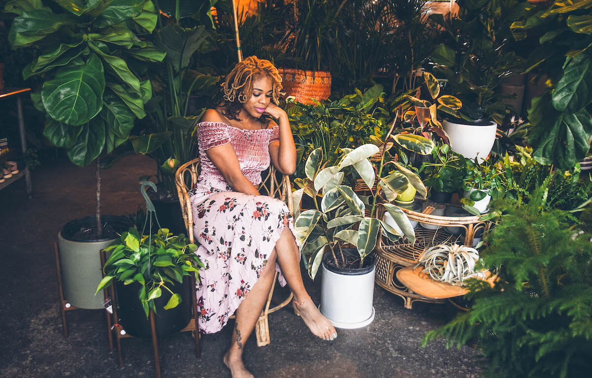 A Black woman in a flowing skirt is sitting on a chair surrounded by a large number of potted plants. She is looking pensive, away from the camera, her head resting on her hand which she is propping up on the chair's armrest. Walls.io free stock photo sites collection.