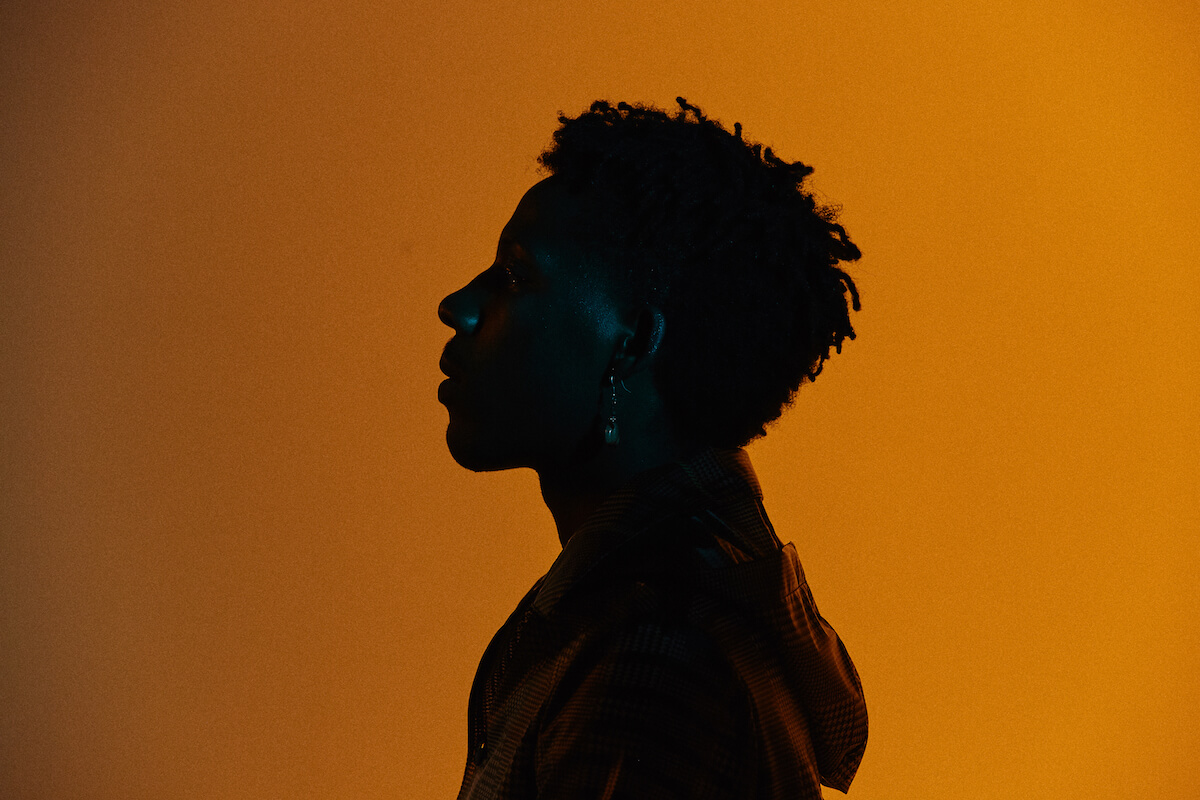 A Black person in profile view is almost silhouetted against an orangeish-yellow background. You can barely recognise their features but it's clear that they're holding their head up proudly. Walls.io free stock photo sites collection.