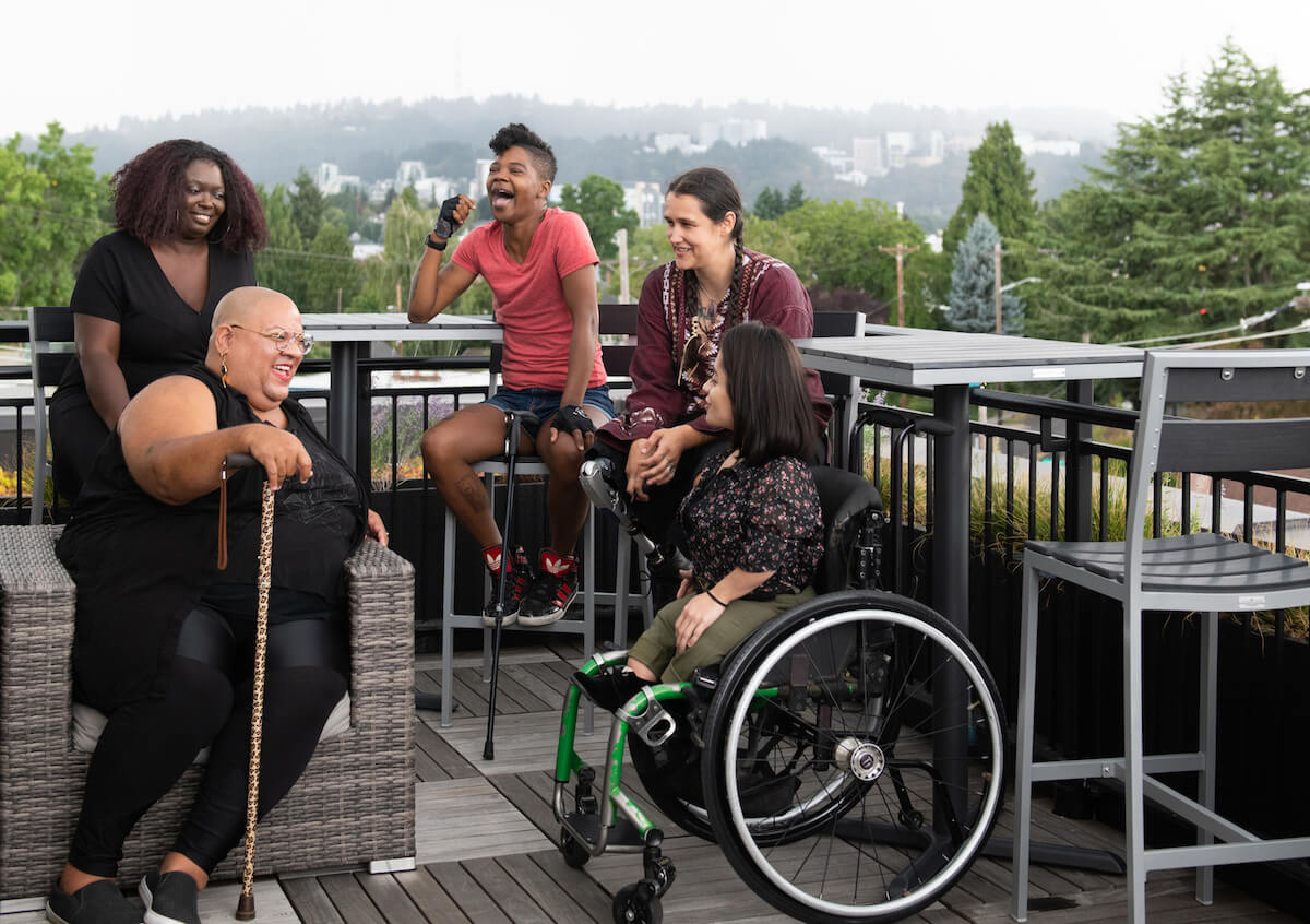 Five disabled people of color with canes, prosthetic legs, and a wheelchair sit on a rooftop deck, laughing and sharing stories. Greenery and city high-rises are visible in the background. Walls.io free stock photo sites collection.