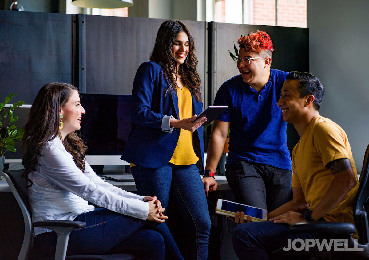 Four people of colour are clustered together in an office, two of them sitting in the foreground, two of them standing in the background. All of them are smiling or laughing. They're wearing colourful clothing and one has vibrant reddish-orange hair. Walls.io free stock photo sites collection.