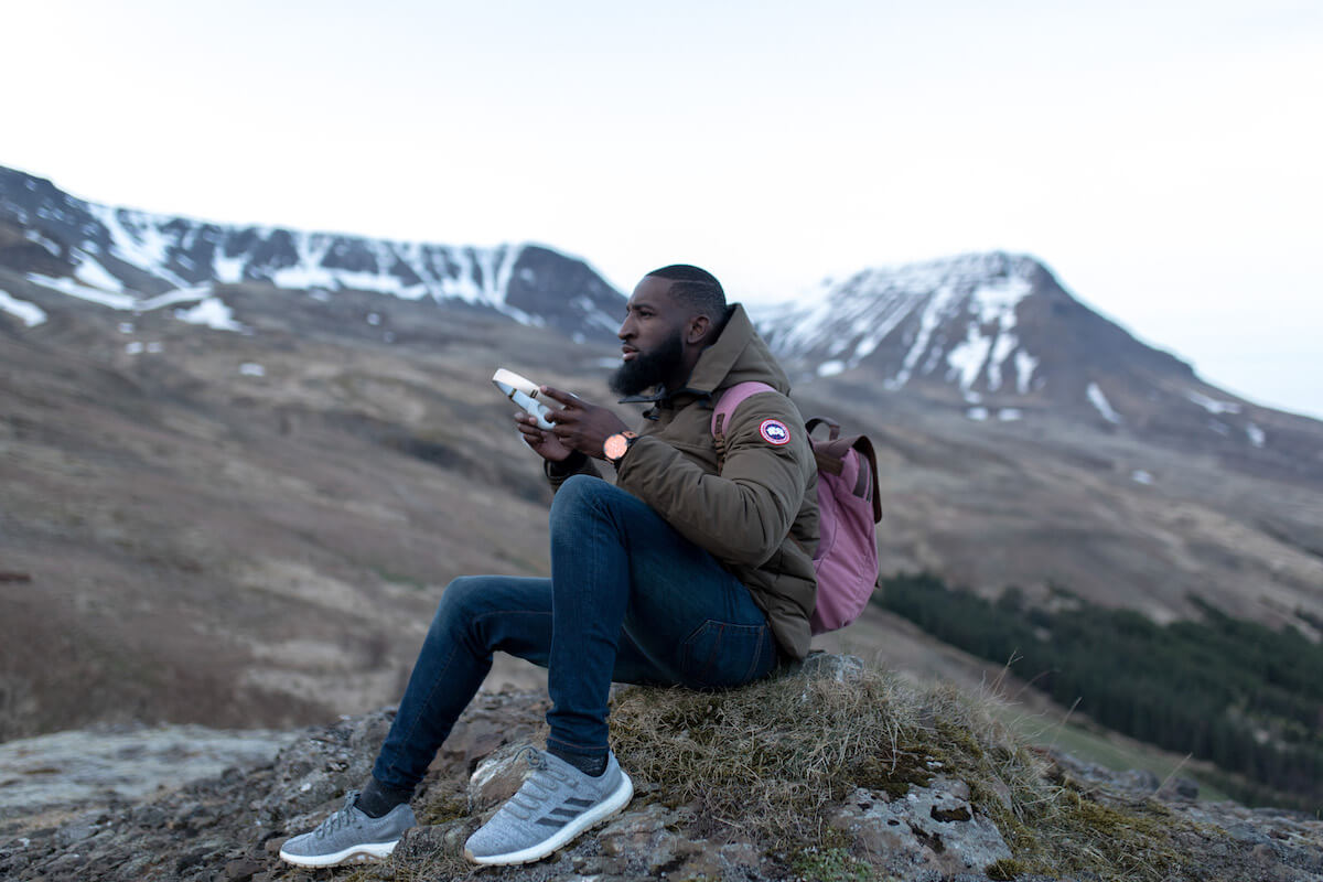 A Black person with a beard is sitting on a hillock surrounded by a somewhat barren mountain landscape. He's wearing trainers, jeans, a puffy brown jacket and a dusky pink backpack. In his hands he's holding a pair of white over-ear headphones. In the background, there's a blurry, snow-capped mountain range. Walls.io free stock photo sites collection.