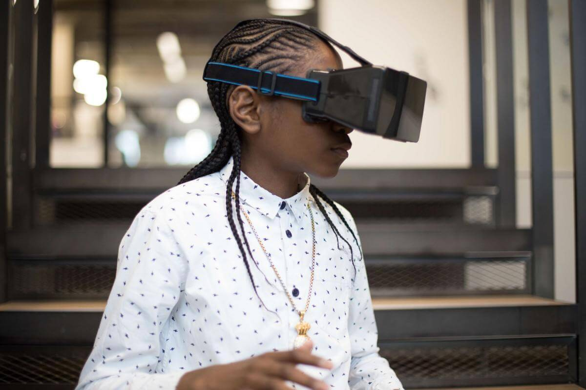 A Black child/teenager is wearing a virtual reality headset. They're clearly absorbed in the activity. Walls.io free stock photo sites collection.