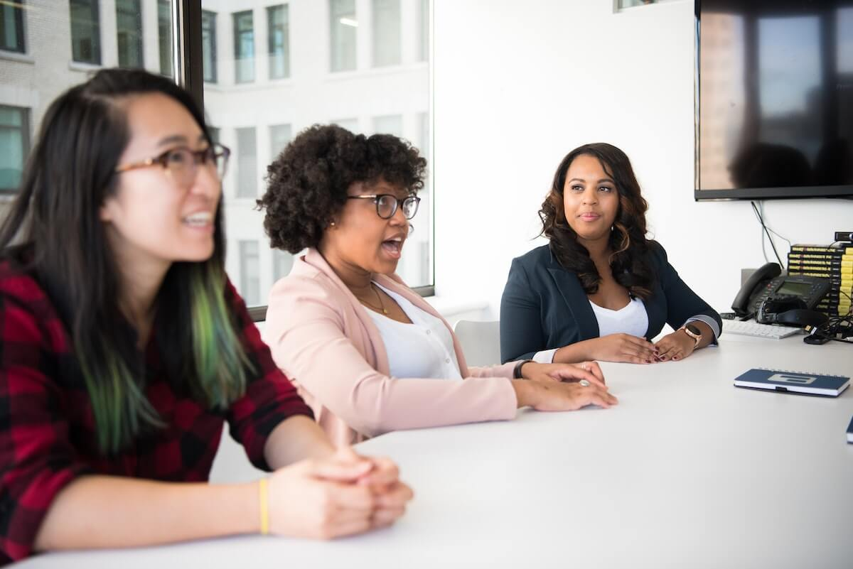Three people of colour are sitting next to each other at a big meeting table. The Black woman with nappy hair in the middle is speaking while the Black woman on her left is looking at her and listening intently. The Asian woman to her right, who's hair lengths are dyed green, is looking at someone off-screen. Walls.io free stock photo sites collection.