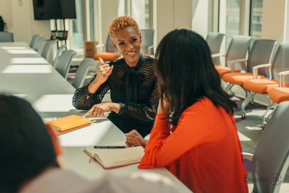 Two women are sitting next to each other at a long meeting table, facing each other. The Black woman with short blonde hair is facing towards the camera and using sign language to talk to the woman who has her back to the camera and is facing the one speaking. Walls.io free stock photo sites collection.