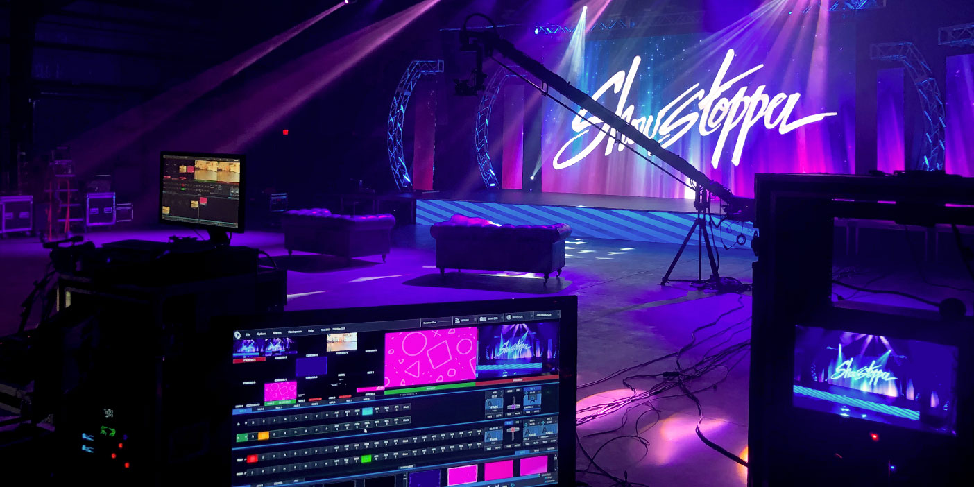 Photo showing the Showstopper stage setup, including sofas in front of the stage as well as the whole live show tech setup behind it.