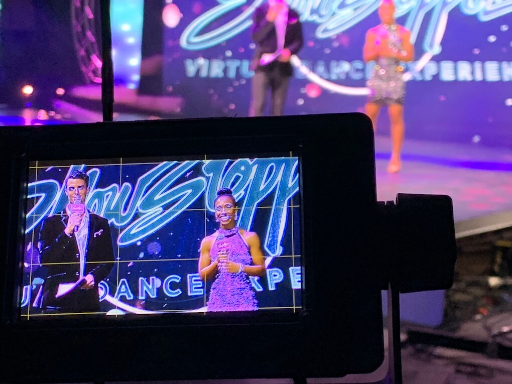 View through the viewfinder of a camera showing the two moderators on the Showstopper stage.