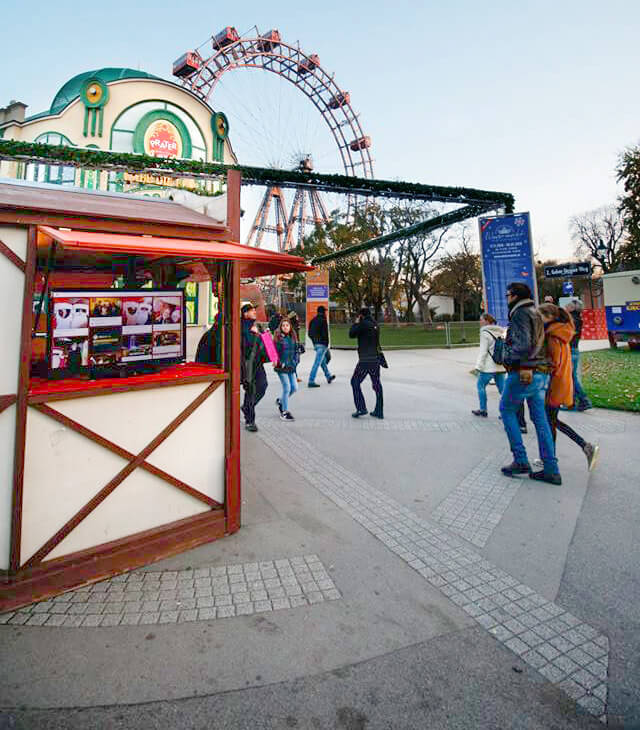 Wichtel Challenge stall at Vienna Prater with the social wall shown on a screen in the booth.