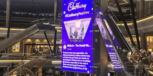Digital signage screen inside a shopping mall displaying a tweet from Cadbury's hashtag marketing campaign #CadburyFestive
