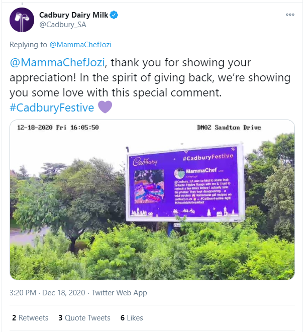 "Billboard between trees displaying a Twitter post from Cadbury's hashtag marketing campaign with the text: ""@MammaChefJozi , thank you for showing your appreciation! In the spirit of giving back, we're showing you some love with this special comment. #CadburyFestive Purple heart "" showing a picture of Cadbury chocolate beneath a Christmas tree"