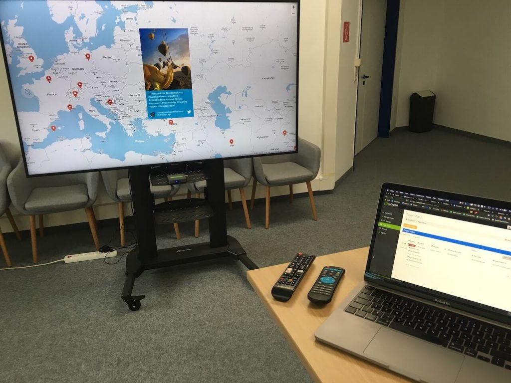 A picture of a TV showing a map layout social media screen set up with the truDigital digital signage app and Walls.io