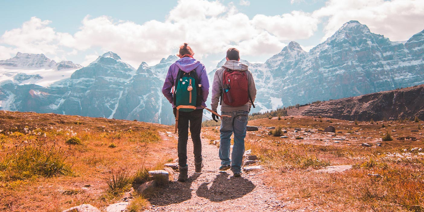 Two people with backpacks walking on a hiking path.