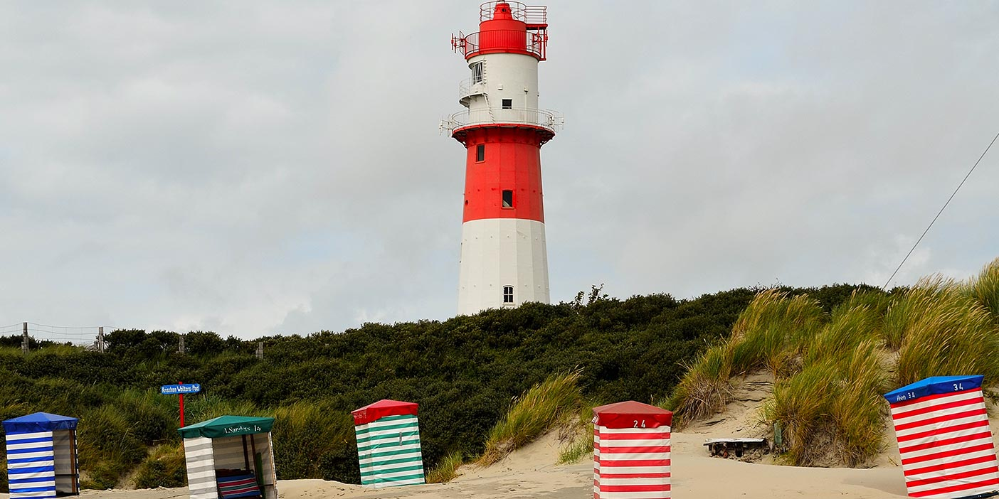 Photo of a red-and-white lighthouse on Borkum standing in the thicket in the background. In the foreground, colourfully striped beach chairs/huts dot the sandy dunes.