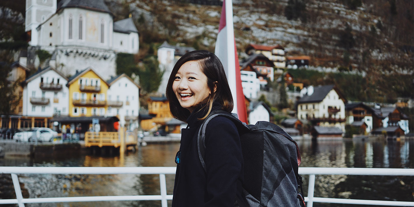 A young person, smiling broadly towards the camera, is standing by the railing at the front of a boat. In the background, on the other side of the water, there's a line of typically Austrian houses by the promenade.