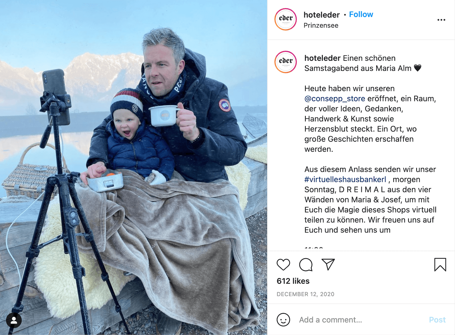 Screenshot of an Instagram post by user @hoteleder showing an adult with a child on their lap facing a smartphone held by a tripod. The two people are wrapped in a blanket and warm clothes. The adult is holding a mug. Behind them, a mountain range is visible.