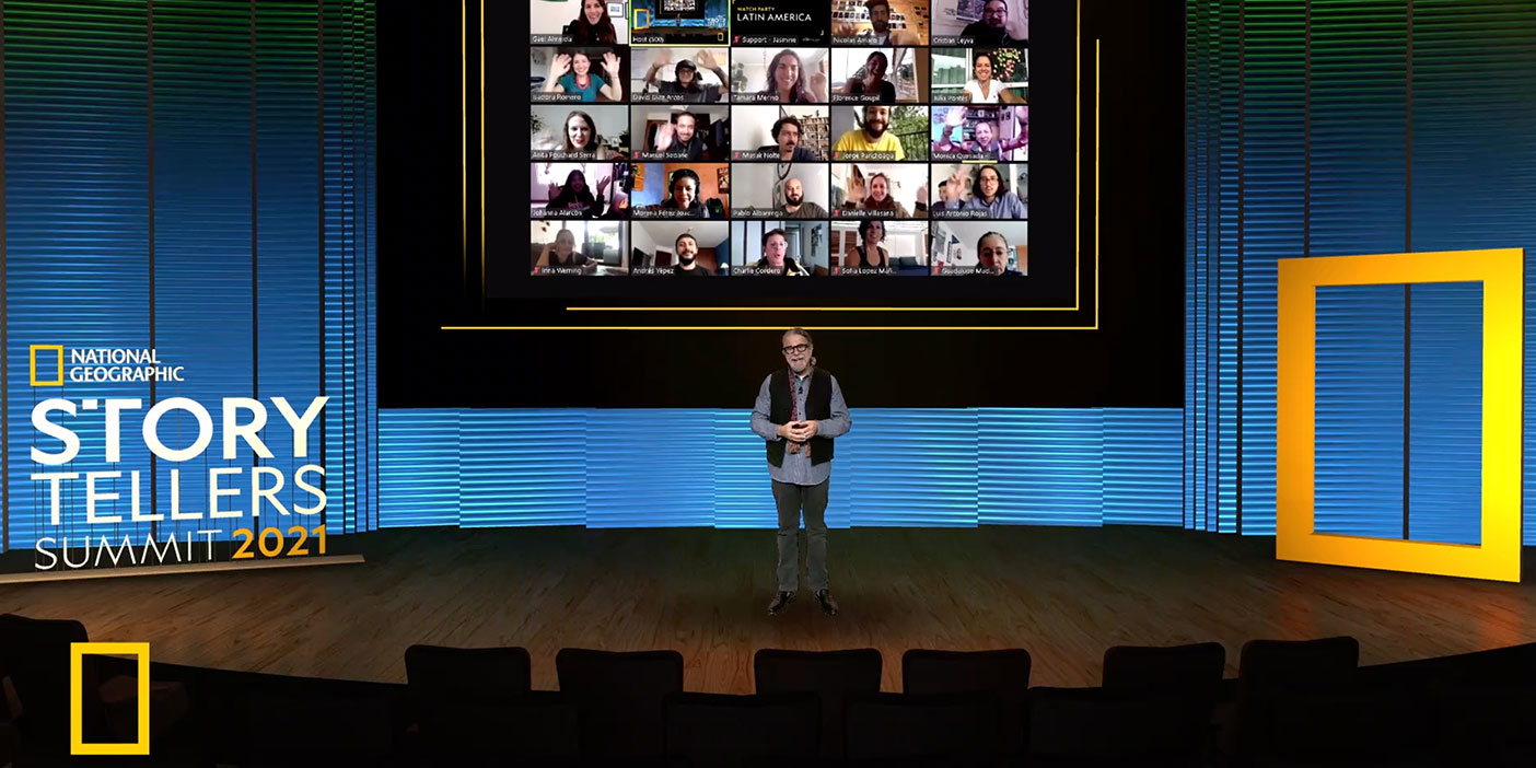 """A presenter is standing on a wide stage. There's no audience in front of them. Behind them, there's a projection of a video call screen with many participants. On the left, a sign says """"National Geographic Storytellers Summit 2021""""."""