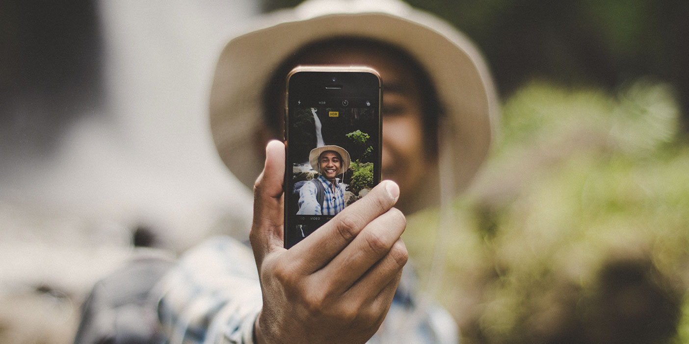A person wearing a hat taking a selfie outdoors.
