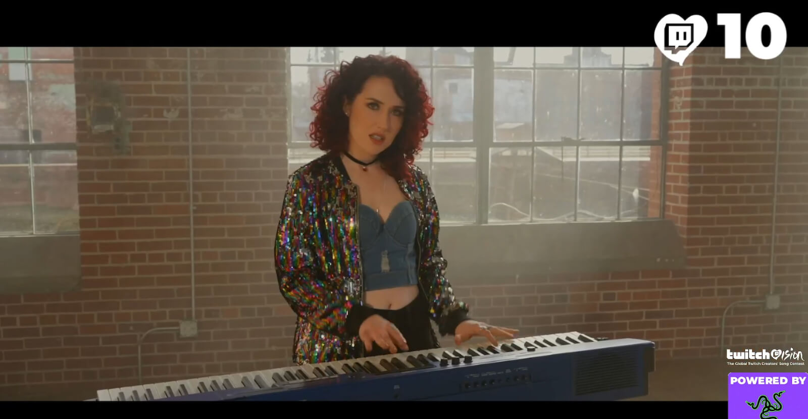 Screenshot from the TwitchVision live-stream showing a creator video. A person with shoulder-length red curly hair and wearing a sparkly colourful jacket is standing behind a keyboard and looking straight at the camera. Behind them is a red brick wall with dirty windows looking a bit like a warehouse.