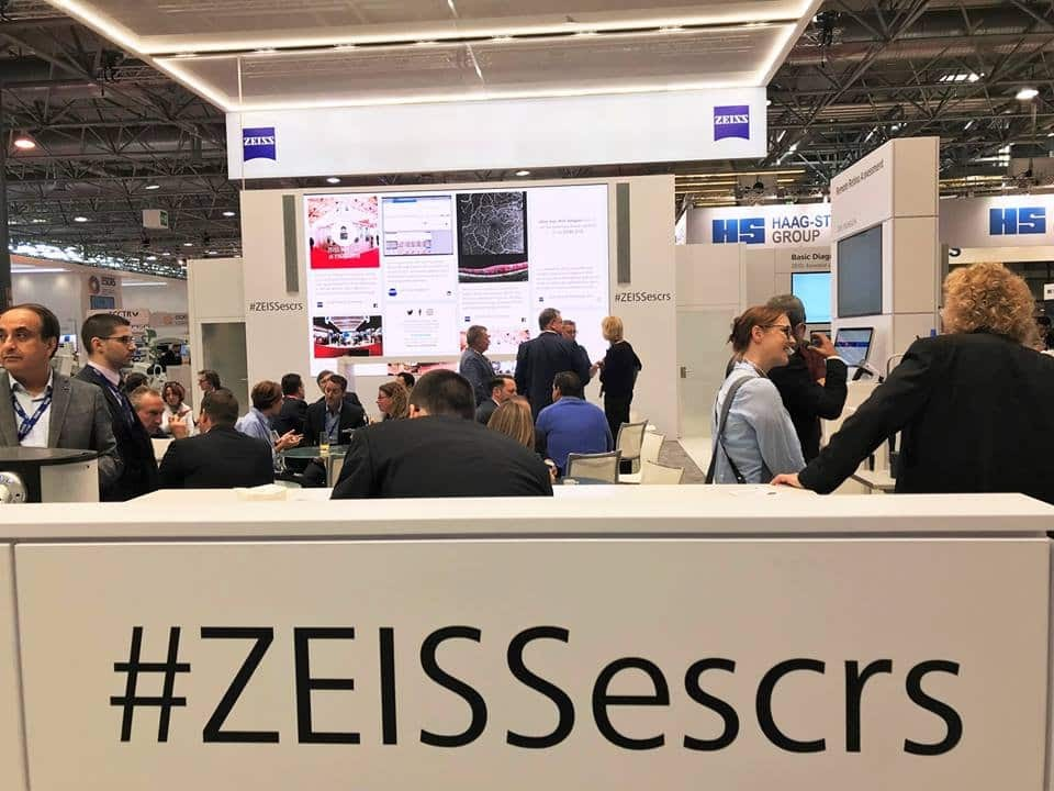 Photo of Zeiss's conference. The image shows a big screen with a social wall, and a big panel with the hashtag #ZEISSescrs.