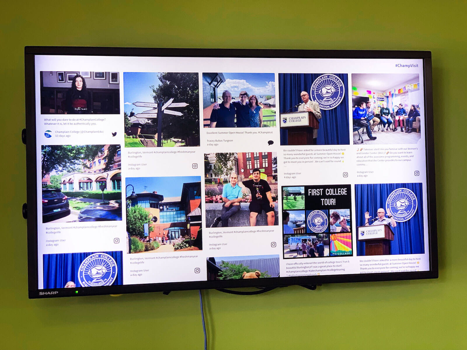 The #ChampVisit social wall shown on a digital signage screen affixed to a green wall.