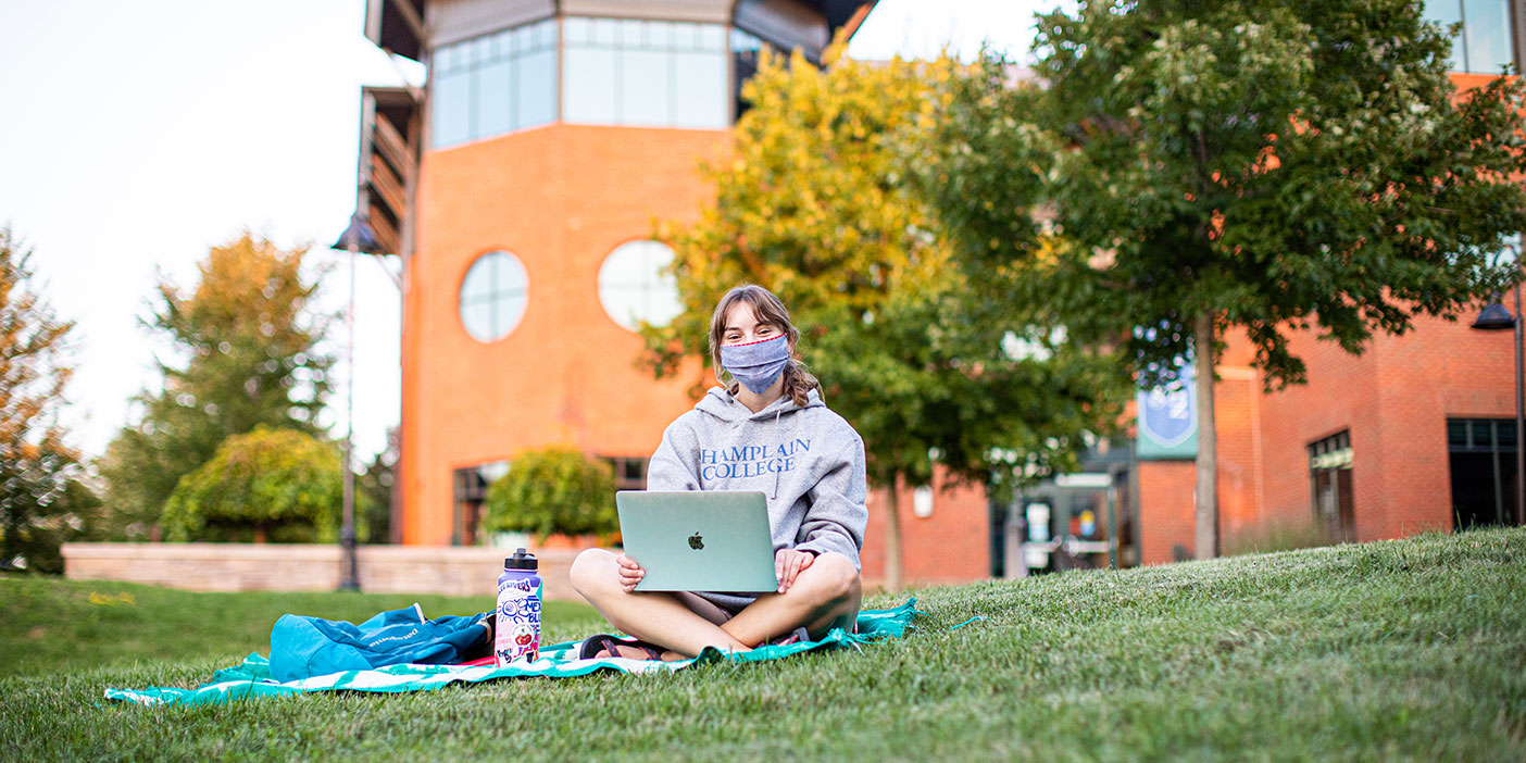 A student wearing a grey Champlain College sweater is sitting on the lawn on a blanket and holding an open laptop on their crossed legs. They're wearing a face mask and looking straight at the camera. In the background, there's a red building and some trees with fall foliage.