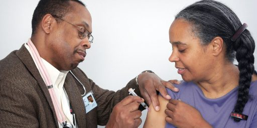 A black doctor giving another black person a vaccination into the shoulder.