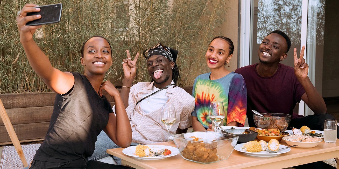 A group of four people taking a selfie at a dining table.