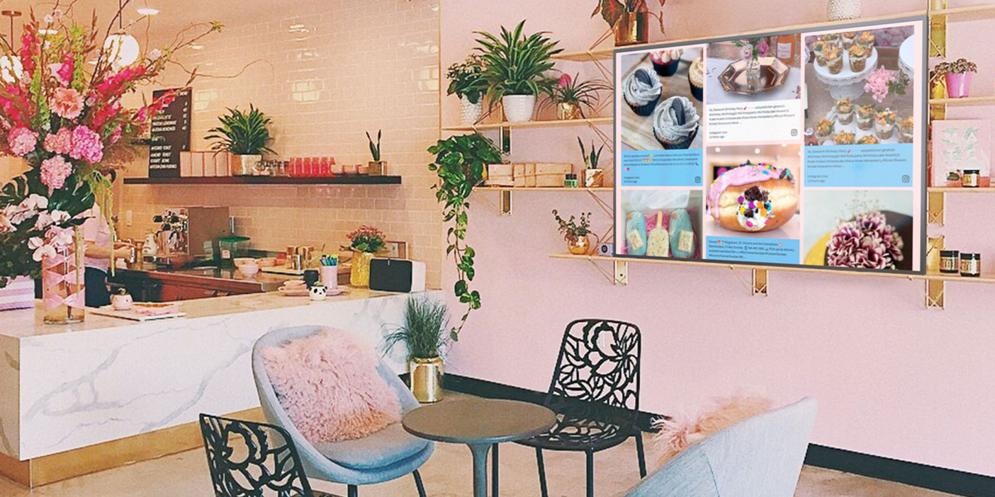 Photo of a cafe with a screen on the wall displaying a live social media feed.