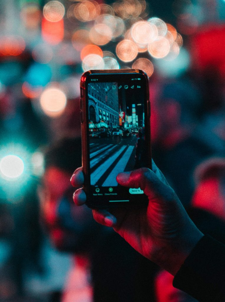 A photo of a hand holding a phone while taking a photo for an Instagram Story of a street at night.