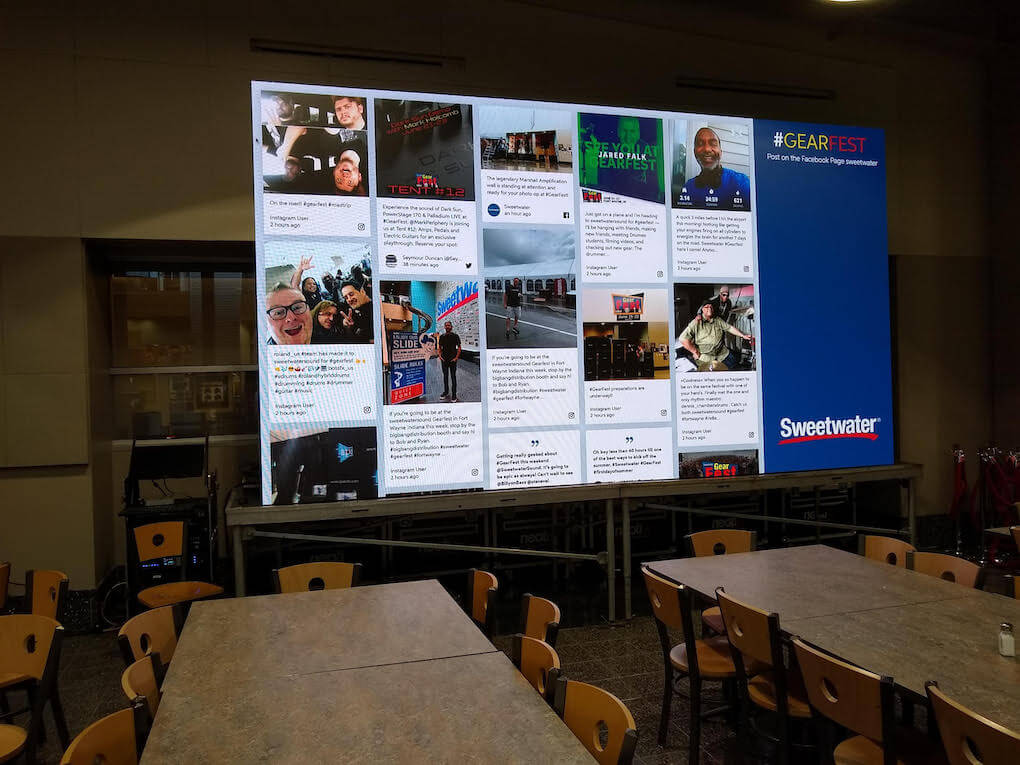 Empty dining hall with Sweetwater's GearFest social media wall displayed prominently on a large screen at the front of the hall.