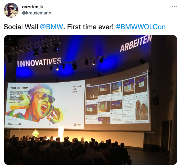 Screenshot of a tweet from an attendee of BMW employee event. The image shows a big screen with a social media wall. A great event example with audience engagement.