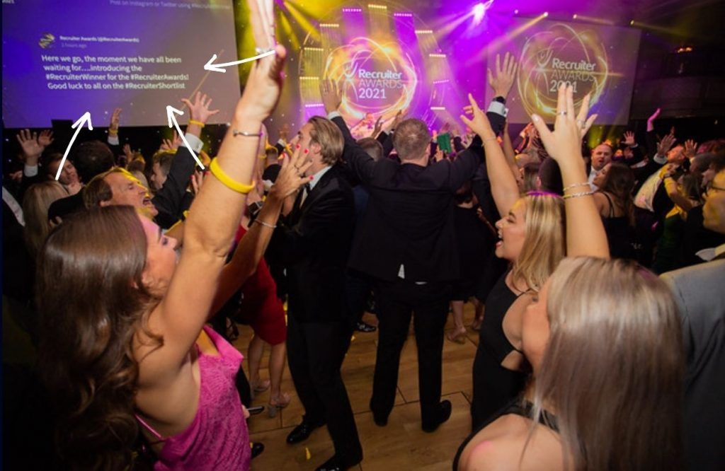 Photo from attendees dancing in front of a screen with a social wall at the Recruiter Awards 2021.